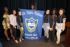 young people holding chi alpha epsilon banner