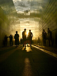 Silhouette of two people walking through a corridor between two tall metal walls covered in etched names at the 9.11 monument in Liberty State Park, with sunset and clouds in the background.